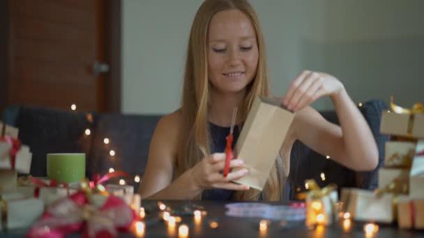 Slowmotion shot egy fiatal nő csomagolási ajándékokat. Jelenleg csomagolt kézműves papírt egy piros és arany szalagot karácsonyra vagy új évet. Nő tesz Adventi naptár a gyermekei