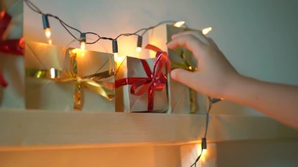 Slowmotion-Aufnahme eines kleinen Jungen nimmt ein Geschenk aus einem Adventskalender, der an einem Bett hängt, das mit Weihnachtsbeleuchtung aufgehellt ist. Vorbereitung auf Weihnachten und Neujahr Konzept. Adventskalender