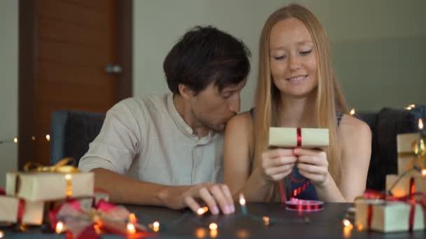 Slowmotion Schuss einer jungen Frau und Mann Vater und Mutter wickeln Geschenke. Geschenke in Handwerkspapier mit einem rot-goldenen Band für Weihnachten oder Neujahr verpackt. Eltern machen einen Adventskalender für