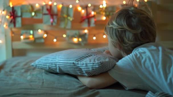 Slowmotion-Aufnahme eines kleinen Jungen wacht auf und sieht einen Adventskalender, der mit Weihnachtsbeleuchtung auf einem Bett aufleuchtet. Vorbereitung auf Weihnachten und Neujahr Konzept. Adventskalenderkonzept