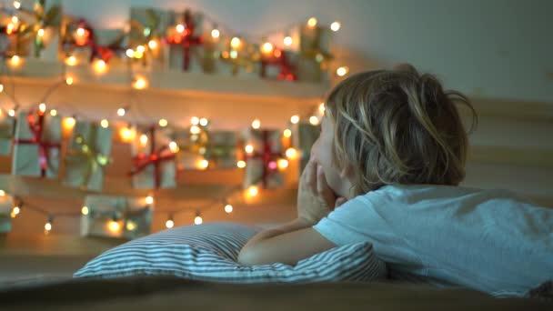 Slowmotion-Aufnahme eines kleinen Jungen, der einen Adventskalender anschaut, der an einem Bett hängt, leuchtet mit Weihnachtsbeleuchtung. Vorbereitung auf Weihnachten und Neujahr Konzept. Adventskalenderkonzept