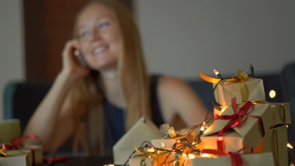 Mladá ženská se předvádí a mluví na mobil. Dárek zabalený do řemeslných papírů s červenou a zlatou stuhou pro Vánoce nebo nový rok. Zaměření je na dárky