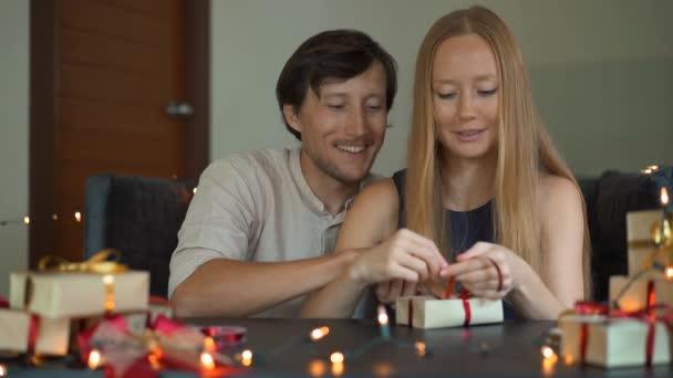 Zeitlupenaufnahme einer jungen Frau und eines Mannes, die Vater und Mutter Geschenke umhüllen. Geschenke eingewickelt in Bastelpapier mit einem rot-goldenen Band für Weihnachten oder Neujahr. Eltern basteln Adventskalender für