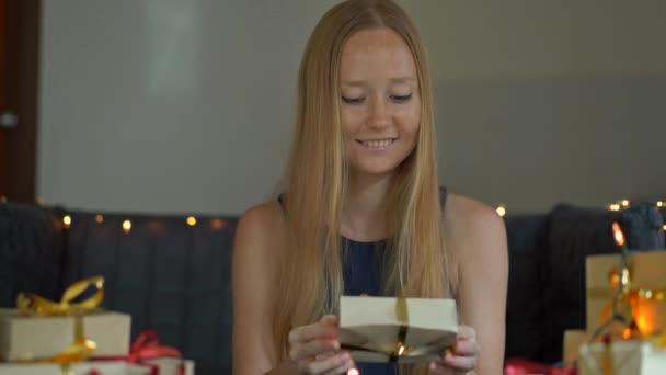 Eine junge Frau packt Geschenke. Geschenk verpackt in Handwerkspapier mit einem roten und goldenen Band für Weihnachten oder Neujahr. Frau macht einen Adventskalender für ihre Kinder