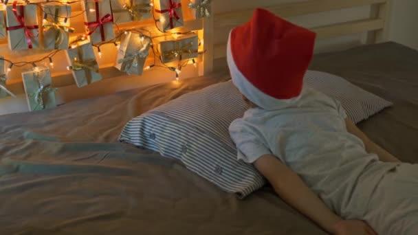 Der kleine Junge wacht auf und sieht einen Adventskalender, der mit Weihnachtsbeleuchtung auf einem Bett aufleuchtet. Vorbereitung auf Weihnachten und Neujahr Konzept. Adventskalenderkonzept