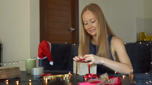 Egy fiatal nő csomagolási ajándékokat. Jelenleg csomagolt kézműves papírt egy piros és arany szalagot karácsonyra vagy új évet. Nő tesz Adventi naptár a gyermekei