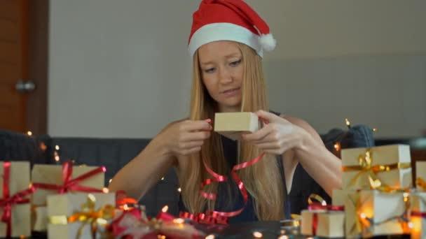 V balení mladé ženy dárky. Dárek zabalený do řemeslných papírů s červenou a zlatou stuhou pro Vánoce nebo nový rok. Žena dělá Adventní kalendář pro své děti