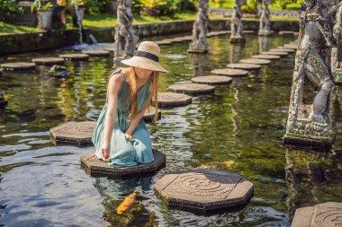 Young woman tourist in Taman Tirtagangga, Water palace, Water park, Bali Indonesia