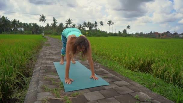 Popomalé vystřelování mladé ženy, která cvičila jóga na krásné rýžové poli