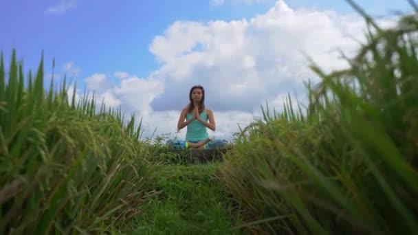 Steadicam záběr mladé ženy dělá meditaci pro Muladhara čakra v balijském způsobem