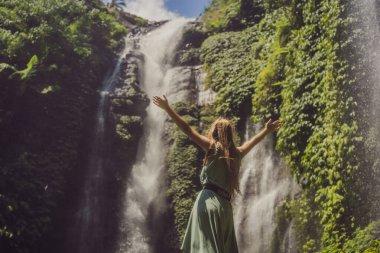 Woman in turquoise dress at the Sekumpul waterfalls in jungles on Bali island, Indonesia. Bali Travel Concept