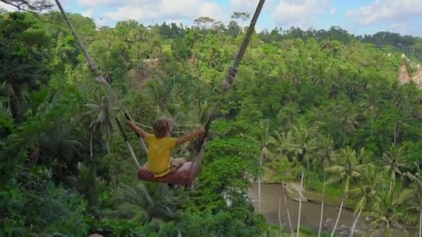 kleiner Junge schaukelt auf Schaukeln in tropischer Umgebung. Anreise zum bali concept