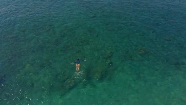 Letecký snímek ženy šnorchlování v krásném tyrkysovém moři