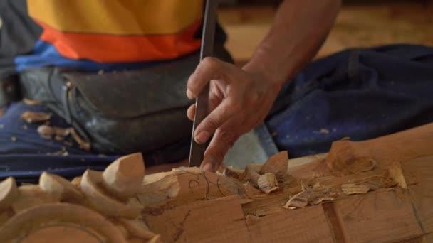 Closeup shot of a master craftsman doing traditional wood carving