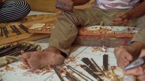 Detailní záběr mistra řemeslníka, který dělá tradiční řezbu dřeva