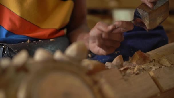 Slowmotion closeup shot of a master craftsman doing traditional wood carving