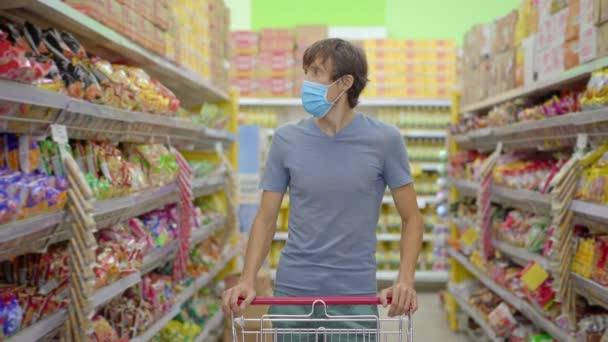 Ein alarmierter Mann trägt beim Einkauf im Supermarkt oder Geschäft eine medizinische Maske gegen Coronavirus. Die Quarantäne ist vorbei, jetzt kann man ins Bekleidungsgeschäft gehen, muss aber einen Mundschutz tragen. Gesundheit