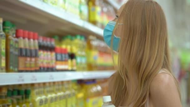 Alarmierte Frau trägt medizinische Maske gegen Coronavirus beim Einkauf im Supermarkt oder Geschäft. Die Quarantäne ist vorbei, jetzt kann man ins Bekleidungsgeschäft gehen, muss aber einen Mundschutz tragen. Gesundheit