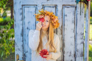 Outdoors lifestyle close up portrait of charming blonde young woman wearing a wreath of autumn leaves. Wearing stylish knitted pullover. Wreath of maple leaves