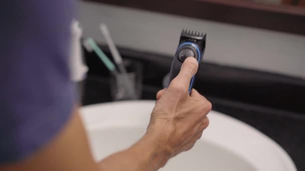 Detailní záběr mladého muže, který si holí vousy pomocí zastřihovače vousů