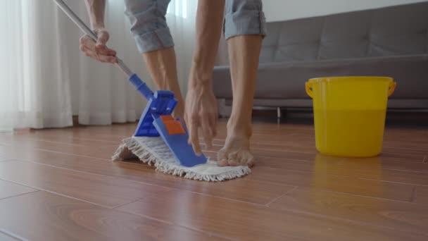 Mladý muž umývá podlahu v bytě. Koncept úklidové služby. Koncept rovnosti pohlaví