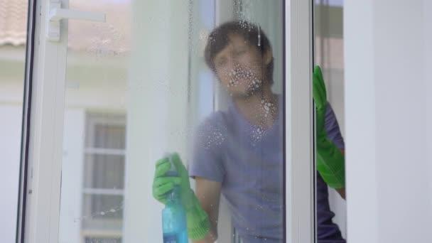Mladík myje v oknech gumových rukavic čisticí kapalinu. Koncept úklidové služby