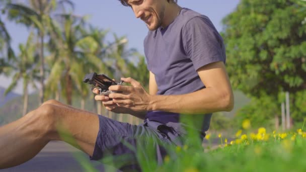 A young man operates a drone sitting on a grass in a tropical surrounding. Aerial photography or videography concept