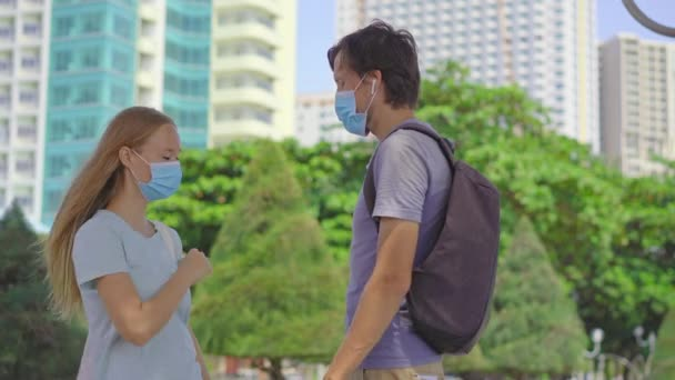 A man in a face mask is trying to hug a woman also wearing a face mask but she doesnt let him because that violates social distancing safety guidelines. Social distancing concept. Covid-19 self