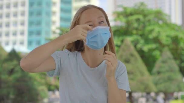 Mladá žena na ulici s maskou na obličeji, aby se chránila před Covidem-19. Žena se chová špatně, dotkne se a poškrábe se na obličeji a masce