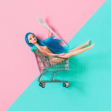 Blue-haired plastic doll girl sitting astride grocery cart on a pink and blue background. Creative food concept.