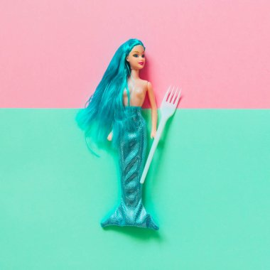 green mermaid doll with long hair lying on double background with plastic forks. creative minimal concept of sea fish food