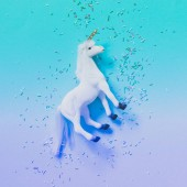 white unicorn with Golden horn on blue background with confetti