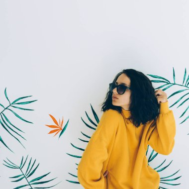 Pretty woman in sunglasses and sweatshirt. Stylish Hoody yellow trendy vibes. Fashion pose