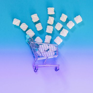 Marshmallows fall from the supermarket cart on the gradient and holographic background