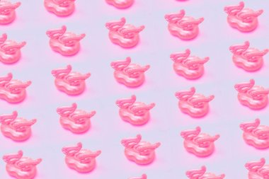 Inflatable heart shape pool toy pattern on pastel pink background. Abstract minimal