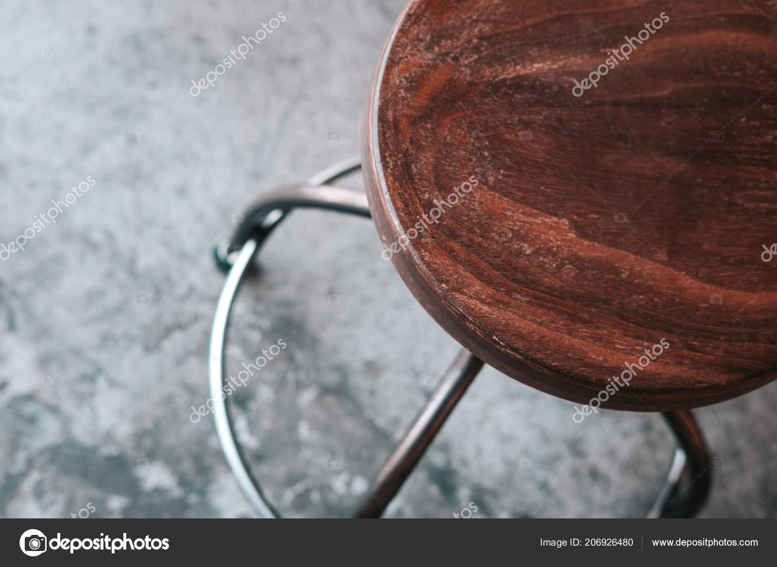 Legno metallo senza schiena sgabello sul pavimento cemento grigio