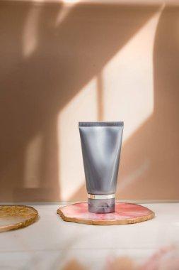 Işık nötr pastel arka planda gri kozmetik tüp, ışıklar ve gölgeler. Doğal minimalizm, temiz. Minimal natürmort. Güzellik günlüğü, markalaşma düzeni, cilt bakımı maketi, boşluk kopyalama