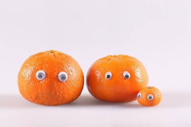 tangerines with eyes of different sizes on a white background