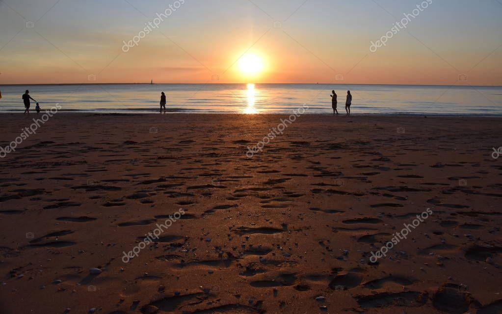 People enjoy the sunset at Mindil Beach. The Sun casts orange shades across an evening sky at Mindil Beach (Darwin, Northern Territory, Australia).