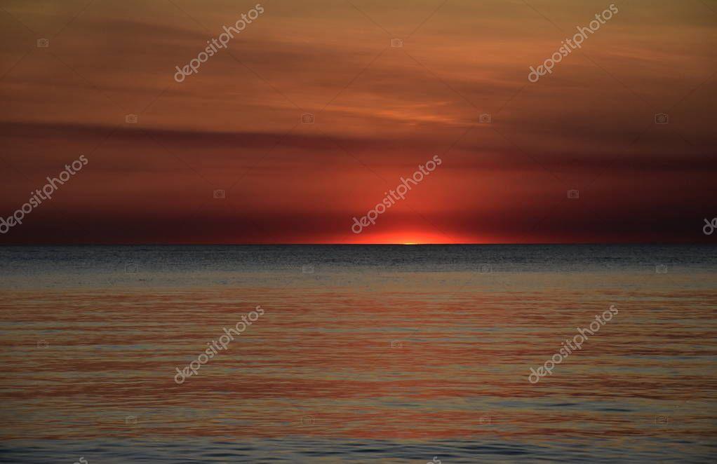 Sun casts orange shades across an evening sky at Mindil Beach (Darwin, Northern Territory, Australia).