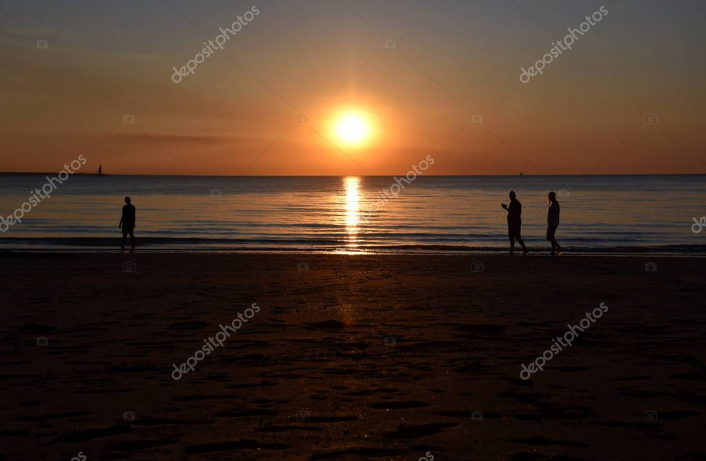 People enjoy the sunset at Mindil Beach. The Sun casts orange shades across an evening sky at Mindil Beach (Darwin, Northern Territory, Australia).
