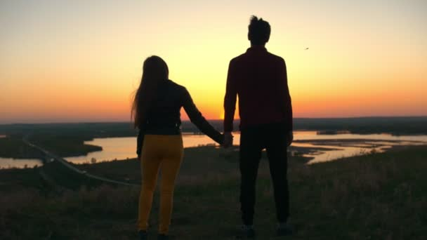 Young couple holding hands on the hill watching the amazing sunset