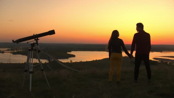 Telescope stands in front of couple holding hands on the hill at the amazing sunset