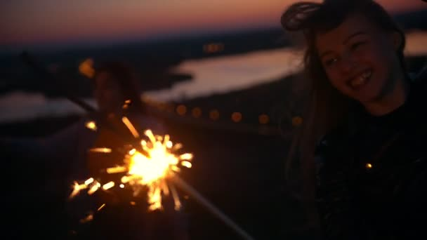 Happy young woman laughing with sparkler on a hill in summer evening at sunset