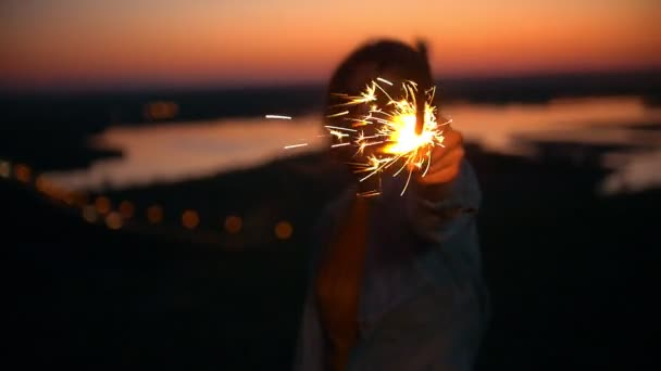 Smiling young woman with sparkler at summer sunset on the hill