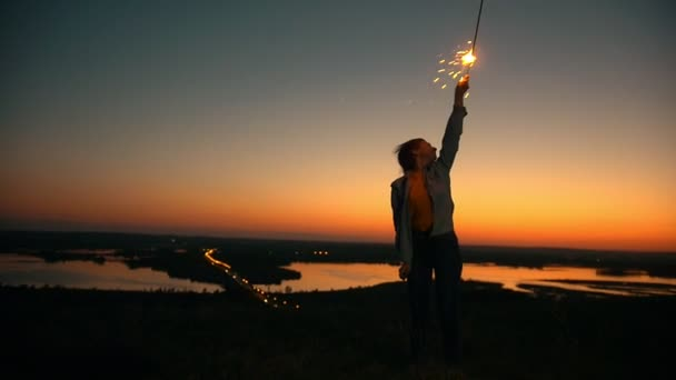 Young woman raising hand with sparkler at amazing sunset on the hill