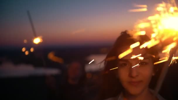 Smiling young woman looking at camera holding sparkler at summer sunset