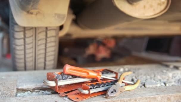 Sada nástrojů před muž pod auto, odšroubování detaily zpod zásobník