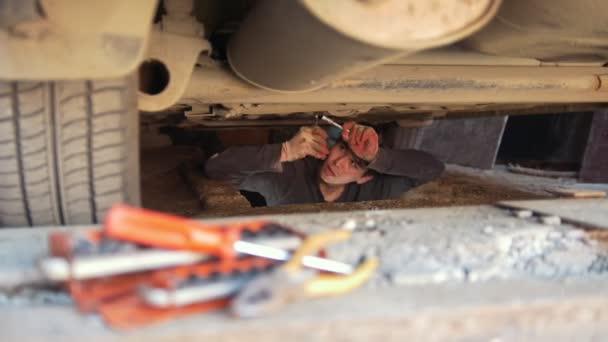 Sada nástrojů před muž pod auto opraví detaily