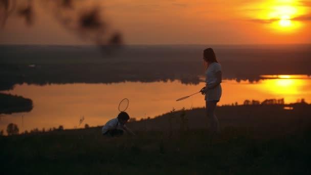 Malý chlapec se svou starší sestrou, hrát badminton na kopci při západu slunce